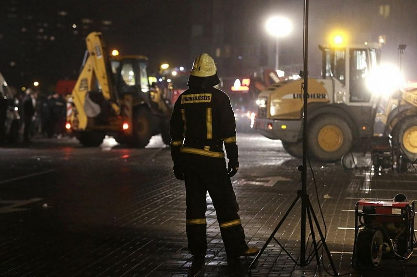 A firefighter watches the rescue operation at the site of the collapsed Maxima supermarket in Riga, Nov 21, 2013. Rescue services said on Friday that 12 people had died after the roof of a supermarket collapsed in the capital, Riga, the previous day.