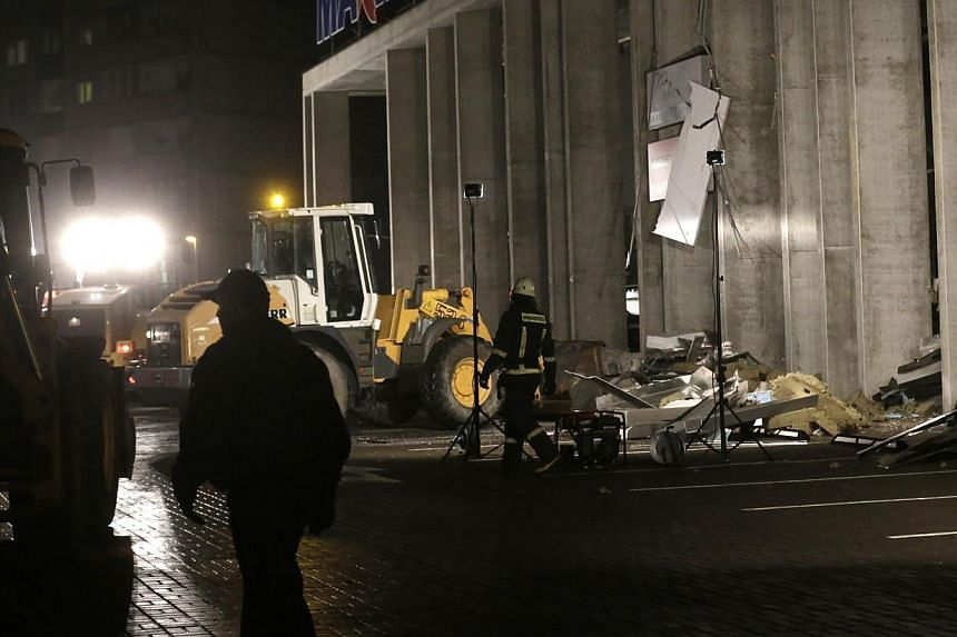 Emergency service unit personnel work at the collapsed Maxima supermarket in Riga, Nov 21, 2013. Rescue services said on Friday that 12 people had died after the roof of a supermarket collapsed in the capital, Riga, the previous day. -- PHOTO: REUTER