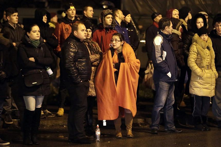 People gather near the collapsed Maxima supermarket in Riga, Nov 21, 2013. Rescue services said on Friday that 12 people had died after the roof of a supermarket collapsed in the capital, Riga, the previous day. -- PHOTO: REUTERS