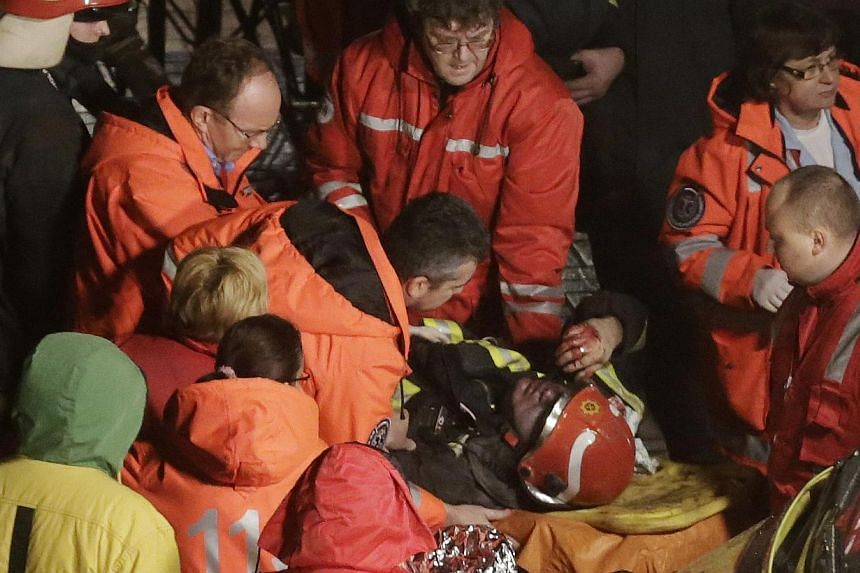 Paramedics inspect a firefighter on a stretcher after he was moved from the collapsed Maxima supermarket in Riga, Nov 21, 2013. Rescue services said on Friday that 12 people had died after the roof of a supermarket collapsed in the capital, Riga, the