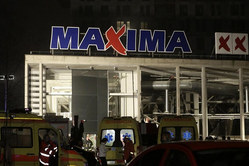 Ambulances are pictured parked near a store with a collapsed roof in Riga, Nov 21, 2013. Rescue services said on Friday that 12 people had died after the roof of a supermarket collapsed in the capital, Riga, the previous day.-- PHOTO: REUTERS