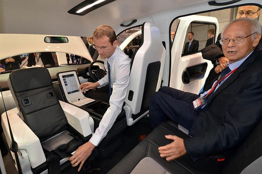 ENERGY-SAVING: The air-conditioning cools seats individually, so when the driver is alone, the whole car need not be cooled.  CHILD-FRIENDLY: National Research Foundation adviser Lui Pao Chuen (above right) in the back seat during a demonstration of