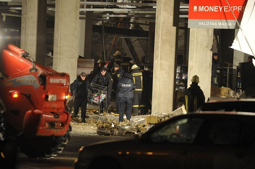 Rescuers search for survivors on Nov 21, 2013, under the rubble at the Maxima supermarket in Riga. Four people were killed and around 30 others injured when the roof of a supermarket collapsed in a suburb of Latvia's capital, emergency services said.