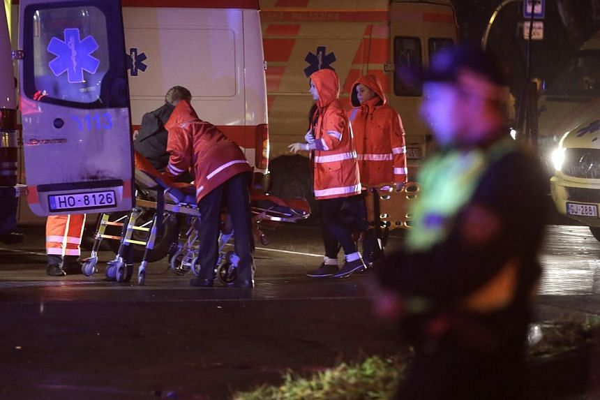 Emergency service medics take care of an injured person near a store with a collapsed roof in Riga, Latvia on Nov 21, 2013. Four people were killed and around 30 others were injured in the incident. -- PHOTO: REUTERS