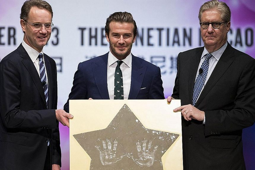 Former England soccer team captain David Beckham displays his hands prints with Marina Bay Sands' President and Chief Executive Officer George Tanasijevich (left), and Sands China' President and CEO Edward Tracy (right) during a promotional event at