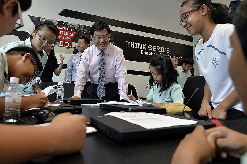 """Minister of Education Mr Heng Swee Keat interacting with Huamin Primary School students inside the Lenovo Lab at Spectra Secondary School, on Nov 12, 2013.The Education Ministry has refined the Primary School Leaving Examination (PSLE), to """"cra"""