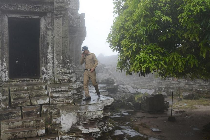 A member of security staff outside one of the buildings inside the Preah Vihear temple complex which is still used as a shrine by local Cambodians. -- ST PHOTO: TAN HUI YEE