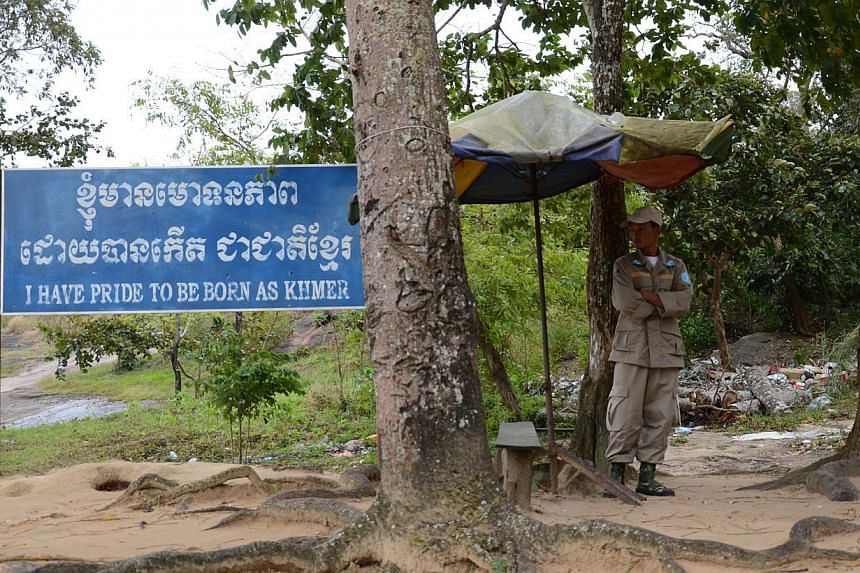 A guard standing next to a banner pronouncing pride in the Khmer identity at the entry point to Preah Vihear temple. -- ST PHOTO: TAN HUI YEE