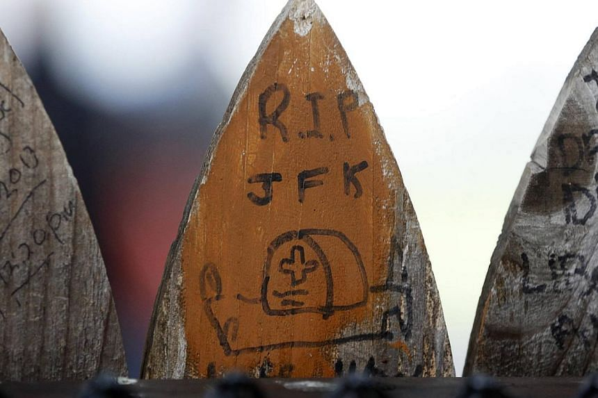 """""""RIP JFK"""" inscriptions meaning """"Rest in Peace, John F. Kennedy"""" adorning slats of the wooden picket fence at the top of the Grassy Knoll in Dealy Plaza in Dallas, on Nov 22, 2013. -- PHOTO: REUTERS"""