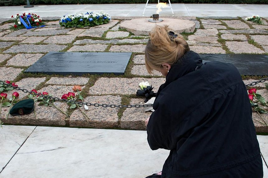 A woman prays at the gravesite of former US President John F. Kennedy at Arlington National Cemetery in Arlington, Virginia, Nov 22, 2013, the 50th anniversary of his assassination. -- PHOTO: AFP