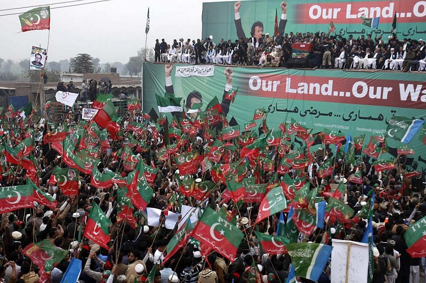 Supporters of the Pakistan Tehreek-e-Insaf (PTI) political party of former cricket star Imran Khan hold party flags and placards during a protest rally to stop Nato supply routes into Afghanistan and drone attacks, in Peshawar November 23, 2013. Mr K