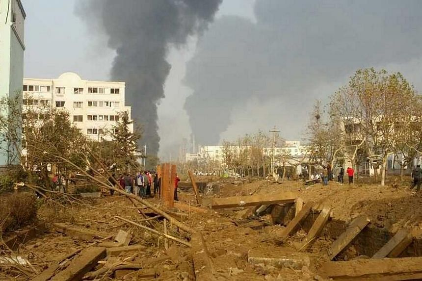 Smoke rises after a pipeline explosion in Huangdao, Qingdao, Shandong province, on Friday, Nov 22, 2013. Some 18,000 people were evacuated from a Chinese coastal city after an oil pipeline explosion killed at least 47 people and sent thick black smok