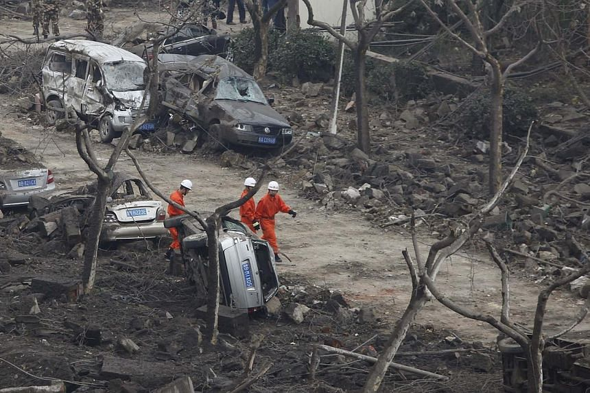 Rescuers search for survivors on a damaged road covered with debris after an explosion in Huangdao, Qingdao, Shandong province, on Friday, Nov 22, 2013. -- PHOTO: REUTERS