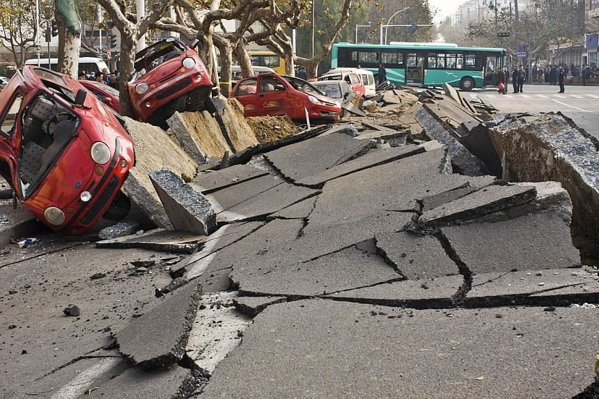 Damaged vehicles lie by a street after an oil pipeline exploded, ripping roads apart, turning cars over and sending thick black smoke billowing over the city of Qingdao, east China's Shandong province, on Friday, Nov 22, 2013. -- PHOTO: AFP