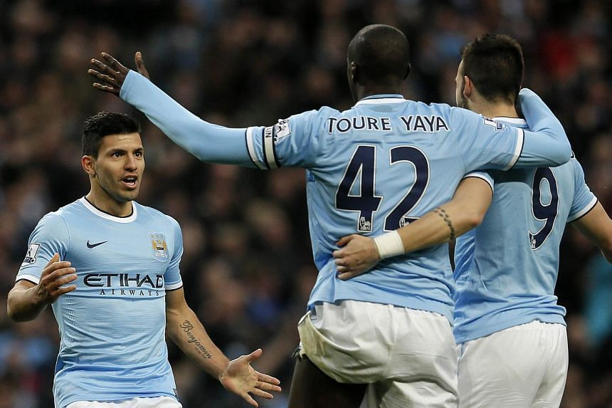 Manchester City's Sergio Aguero (left) celebrates his second goal with Yaya Toure (centre) and Alvaro Negredo during their English Premier League soccer match against Tottenham Hotspur at the Etihad Stadium in Manchesterr, northern England Nov 24, 20