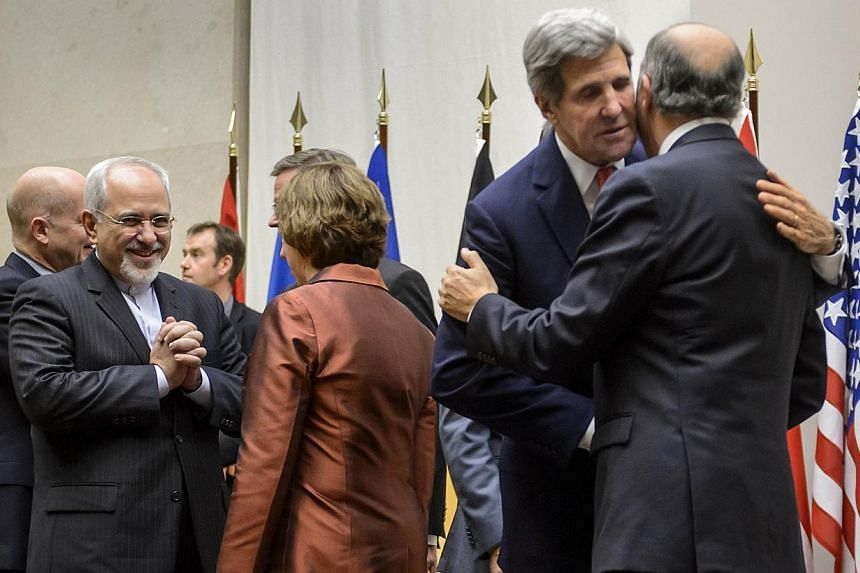 Iranian Foreign Minister Mohammad Javad Zarif (left) reacts next to European Union foreign policy chief Catherine Ashton (centre) as United States Secretary of State John Kerry (second right) embraces French Foreign Minister Laurent Fabius in Geneva