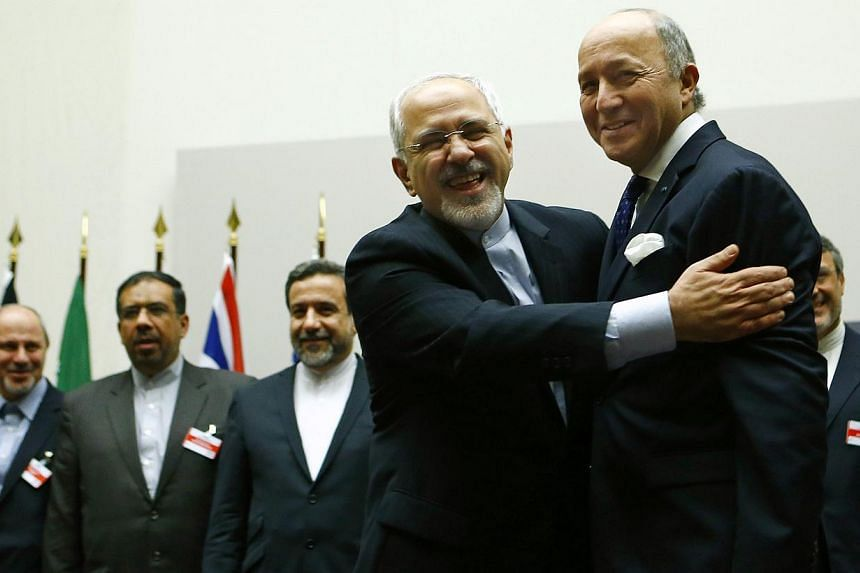 Iranian Foreign Minister Mohammad Javad Zarif (second right) hugs French Foreign Minister Laurent Fabius after a ceremony at the United Nations in Geneva on Nov 24, 2013. Iran and six world powers reached a breakthrough agreement early on Sunday to c