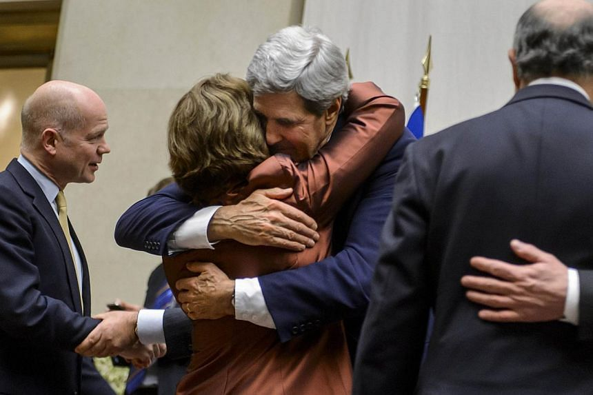 (from left) EU foreign policy chief Catherine Ashton (second left) is embraced by US Secretary of State John Kerry next to British Foreign Secretary William Hague (far left) and French Foreign Minister Laurent Fabius (far R) after a statement on earl