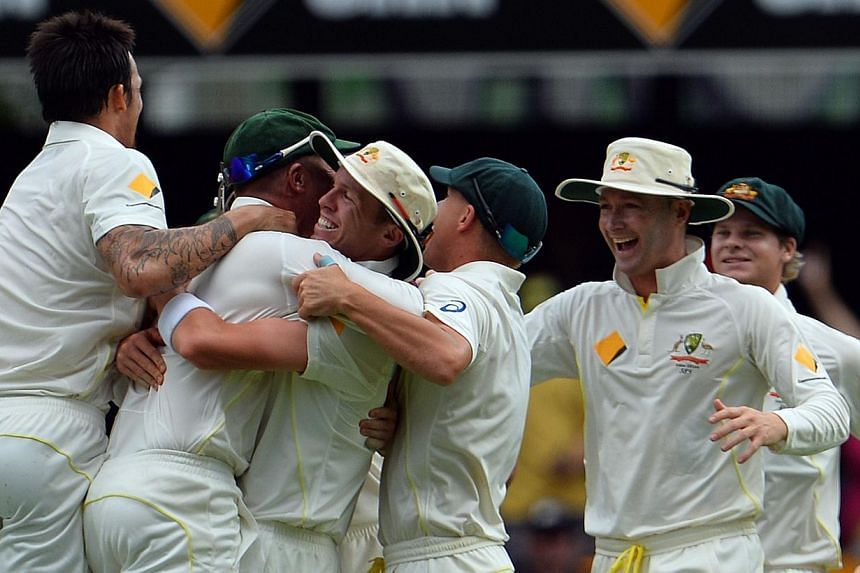 Australian players celebrates the vital dismissal of England's Stuart Broad during the day four of the first Ashes cricket Test match between England and Australia at the Gabba Cricket Ground in Brisbane, on Sunday, Nov 24, 2013. Australia thump