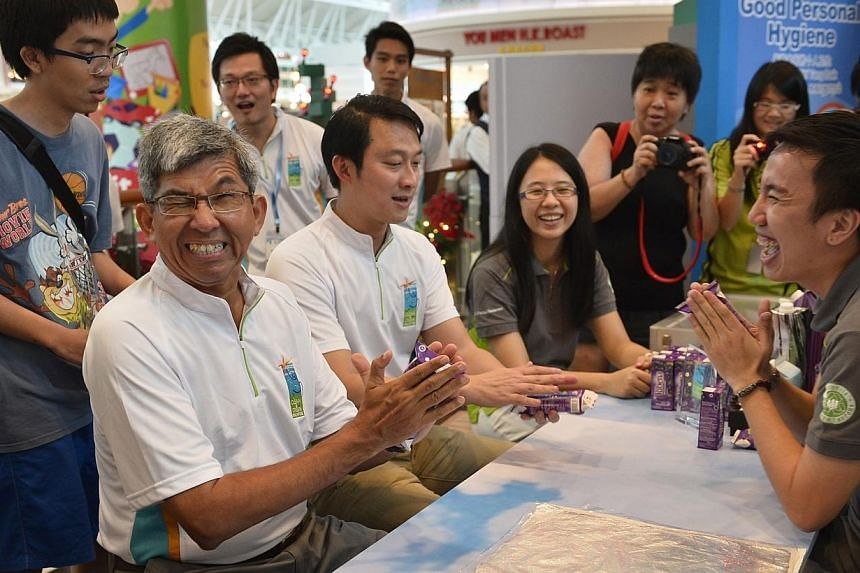Dr Yaacob Ibrahim (left), Minister for Communications and Information, grimaces as he anticipates the tetra pack he is flattening to burst. With him is vice-chairman of Central Singapore CDC Dr Lam Pin Min (second left). They are learning how to coll