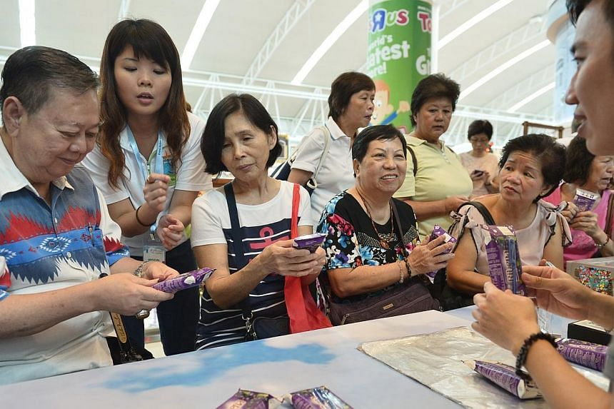 (From left) Mr Wong Fatt Cheong, 68, Mdm Lilian Ang, 65, Mdm Lau Keng Wah, 68, and Mdm Tan Leng Hong, 63, learn how to collapse tetra beverage cartons to save space for disposal and to make recycling easier. -- ST PHOTO: ASHLEIGH SIM