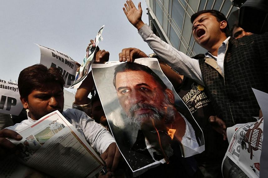 Activists of the Akhil Bharatiya Vidyarthi Parishad (ABVP), linked to India's main opposition Bharatiya Janata Party (BJP), burn a poster of Tarun Tejpal, editor-in-chief of India's leading investigative magazine, during a protest in New Delhi, on Fr