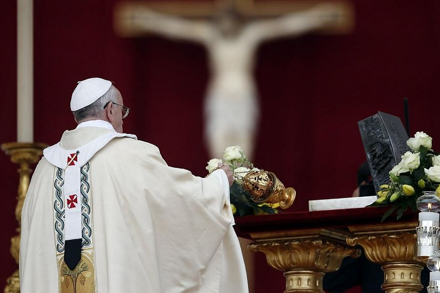Pope Francis blesses the relics of the Apostle Peter on the altar during a mass at St Peter's Square at the Vatican, on Sunday, Nov 24, 2013. -- PHOTO: REUTERS