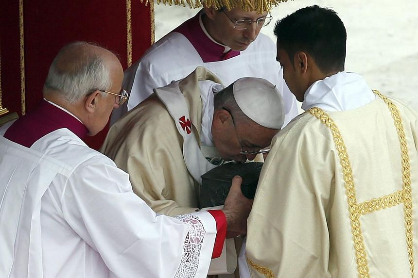 Pope Francis kisses the relics of the Apostle Peter on the altar during a massat St Peter's Square at the Vatican, on Sunday, Nov 24, 2013. -- PHOTO: REUTERS