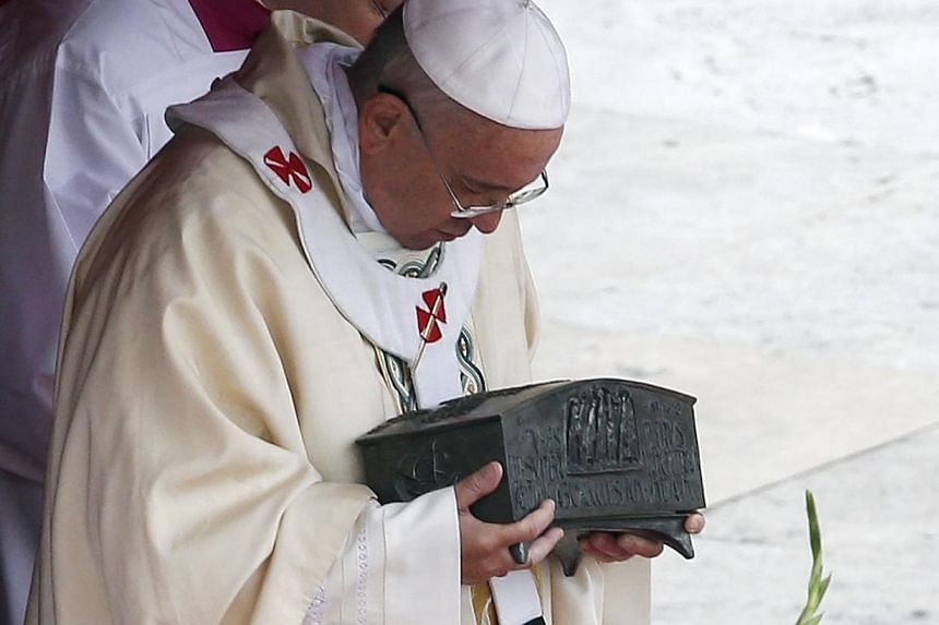 Pope Francis holds the relics of the Apostle Peter on the altar during amassat St Peter's Square at the Vatican, on Sunday, Nov 24, 2013. -- PHOTO: REUTERS