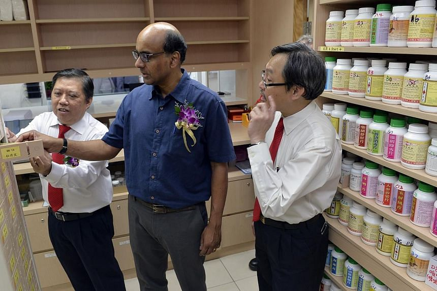 (From left) President of The Public Free Clinic Society Seow Ser Fatt, Deputy Prime Minister and Finance Minister Tharman Shanmugaratnam and Pharmaceutical Officer Tan Ooh Chye inspecting the dispensary of the clinic during a short tour of