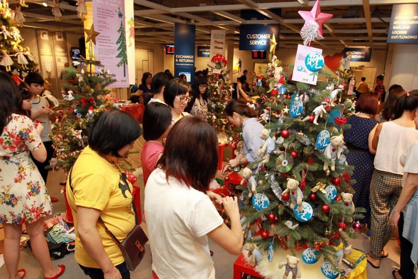 Ten disadvantaged children joined staff from the Singapore Press Holdings (SPH) to decorate Christmas trees to be auctioned for charityat Ikea Alexandra on Sunday, Nov 24, 2013. -- PHOTO: WANBAO