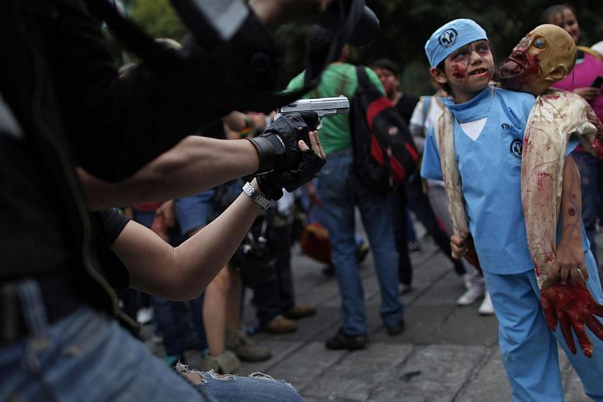"A boy dressed as a zombie takes part in a Zombie Walk procession in Mexico City on Nov 23, 2013. More than 7,000 ""zombies"" crammed Mexico City's streets on Saturday for the popular Zombie Walk Mexico, celebrating connections with the dead. -- PHOTO:"