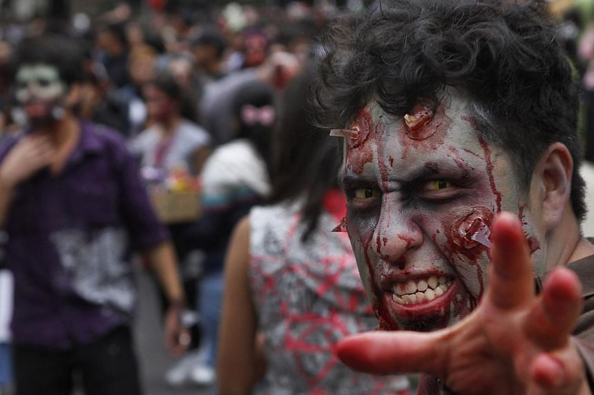 "A man in costume takes part in the Zombie Walk in Mexico City on Nov 23, 2013. More than 7,000 ""zombies"" crammed Mexico City's streets on Saturday for the popular Zombie Walk Mexico, celebrating connections with the dead. -- PHOTO: AP"