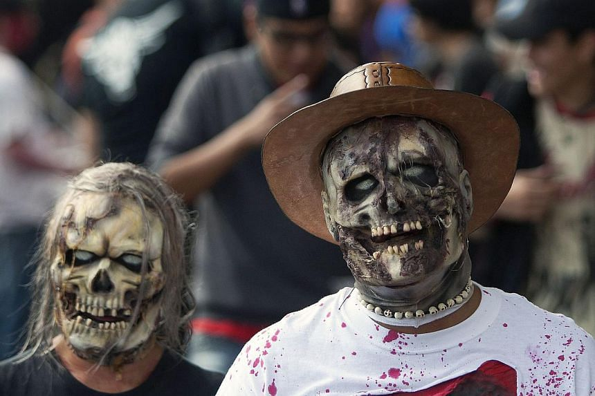 "A couple dressed up as zombies take part in a Zombie Walk in Mexico City on Nov 23, 2013. More than 7,000 ""zombies"" crammed Mexico City's streets on Saturday for the popular Zombie Walk Mexico, celebrating connections with the dead. -- PHOTO: AFP"