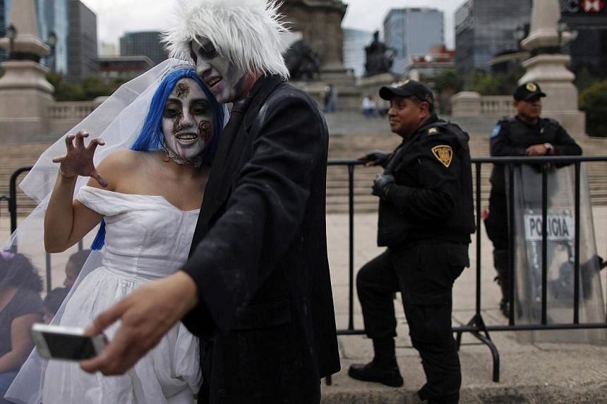 "A couple dressed as zombie bride and groom pose for a photo during a Zombie Walk procession in Mexico City on Nov 23, 2013. More than 7,000 ""zombies"" crammed Mexico City's streets on Saturday for the popular Zombie Walk Mexico, celebrating connection"
