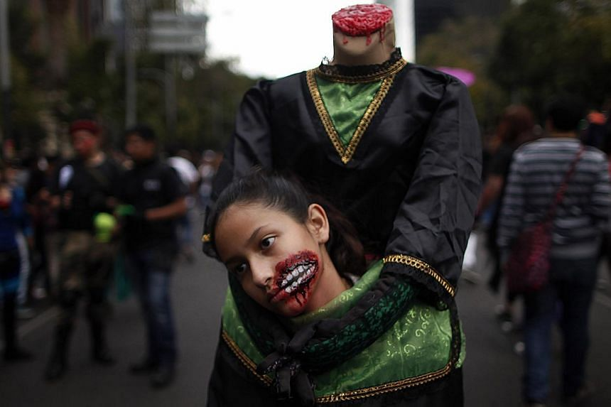 "A girl dressed as zombie takes part during a Zombie Walk procession in Mexico City on Nov 23, 2013. More than 7,000 ""zombies"" crammed Mexico City's streets on Saturday for the popular Zombie Walk Mexico, celebrating connections with the dead. -- PHOT"