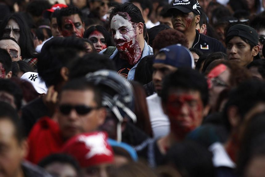 "People dressed as zombies participate in a Zombie Walk procession in Mexico City on Nov 23, 2013. More than 7,000 ""zombies"" crammed Mexico City's streets on Saturday for the popular Zombie Walk Mexico, celebrating connections with the dead. -- PHOTO:"