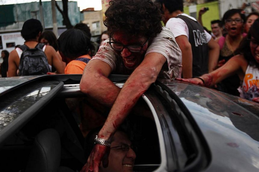"A man dressed as zombie touches the driver of a car during a Zombie Walk procession in Mexico City on Nov 23, 2013. More than 7,000 ""zombies"" crammed Mexico City's streets on Saturday for the popular Zombie Walk Mexico, celebrating connections with t"