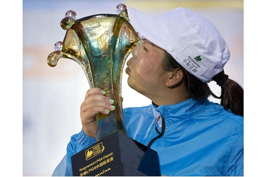 China's Feng Shanshan kisses her trophy after winning the Reignwood LPGA Classic golf tournament at Pine Valley Golf Club on the outskirts of Beijing, China, on Sunday, Oct 6, 2013. Feng fired a bogey-free six-under par 66 on Sunday to win the s