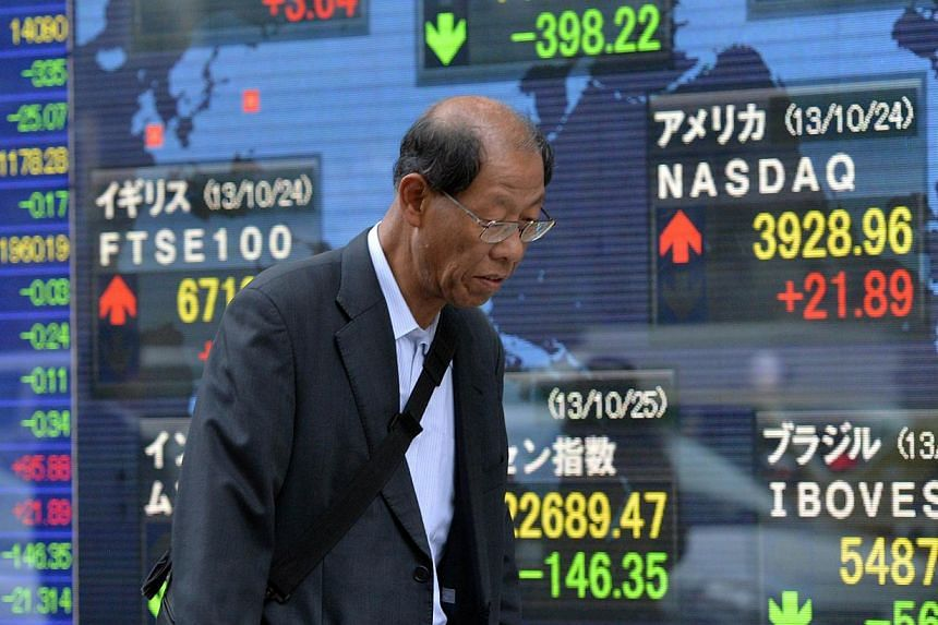A Japanese pedestrian passes before a share prices board in Tokyo on Oct 25, 2013. The yen sank in Asia on Monday as a generally upbeat outlook led dealers into higher-yielding investments, with the euro hitting a four-year high thanks to upbeat Germ