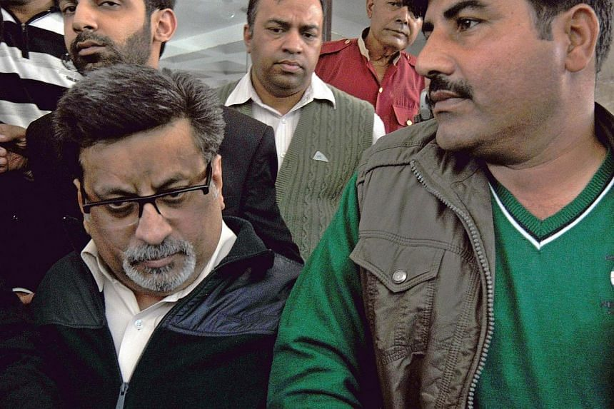 Indian defendant Rajesh Talwar (left) heads to court in Ghaziabad, some 30km east of New Delhi, on Nov 25, 2013. A judge found Talwar and his wife Nupur guilty on Monday of slitting the throats of their teenage daughter and a servant after a mu