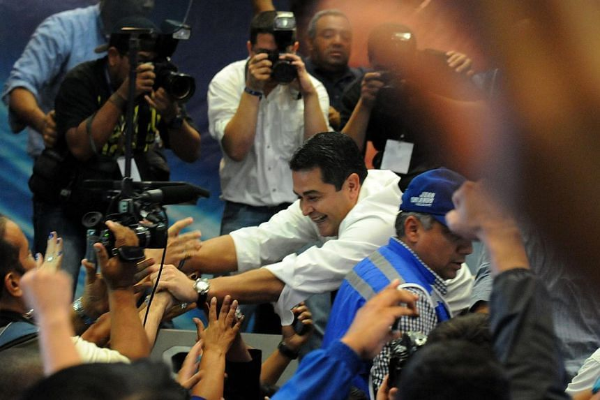 Honduras presidential candidate for the Partido Nacional (PN) Juan Orlando Hernandez celebrates with supporters after claiming victory in the presidential vote, citing official electoral board results in Tegucigalpa on Nov 24, 2013. -- PHOTO: AFP