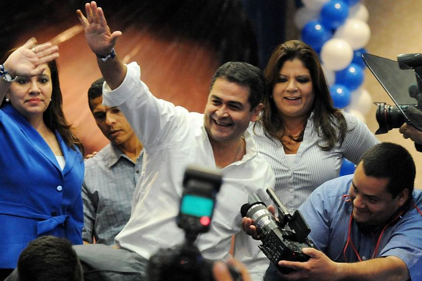 Honduras presidential candidate for the Partido Nacional (PN) Juan Orlando Hernandez celebrates after claiming victory in the presidential vote, citing official electoral board results in Tegucigalpa on Nov 24, 2013. -- PHOTO: AFP