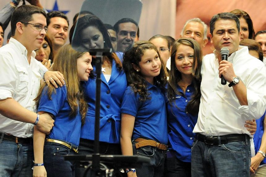 Honduras presidential candidate for the Partido Nacional (PN) Juan Orlando Hernandez celebrates with his family after claiming victory in the presidential vote, citing official electoral board results in Tegucigalpa on Nov 24, 2013. -- PHOTO: AFP