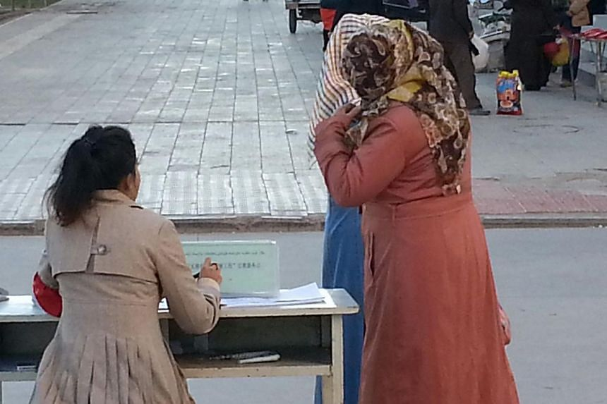 This picture taken on November 9, 2013 shows a Chinese government worker beckons two women to her streetside stand and logs their details under the gaze of a surveillance camera, as their offence: wearing veils, in the ancient Silk Road oasis of Kash