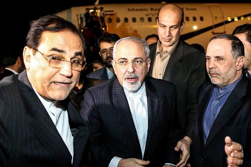 A picture obtained from Iran's ISNA news agency shows Iranian Foreign Minister Mohammad Javad Zarif (centre) arriving at Teheran's Mehrabad Airport after talks in Geneva in which world powers reached an agreement with Iran over its nuclear programme