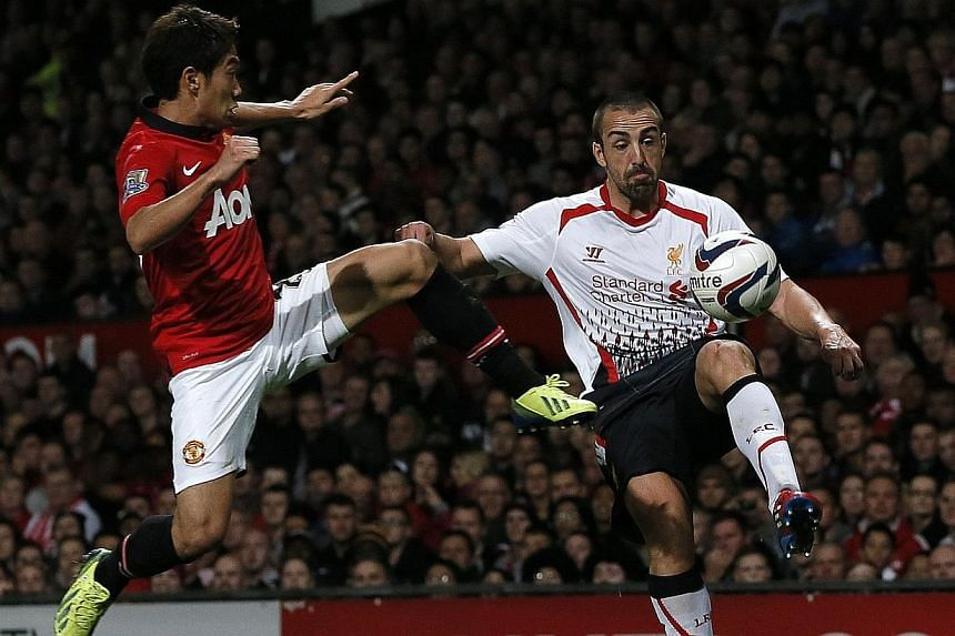 Manchester United's Shinji Kagawa (left) challenges Liverpool's Jose Enrique during their English League cup soccer match against Liverpool at Old Trafford in Manchester, northern England, on Sept 25, 2013. Liverpool left-back Jose Enrique will be ou
