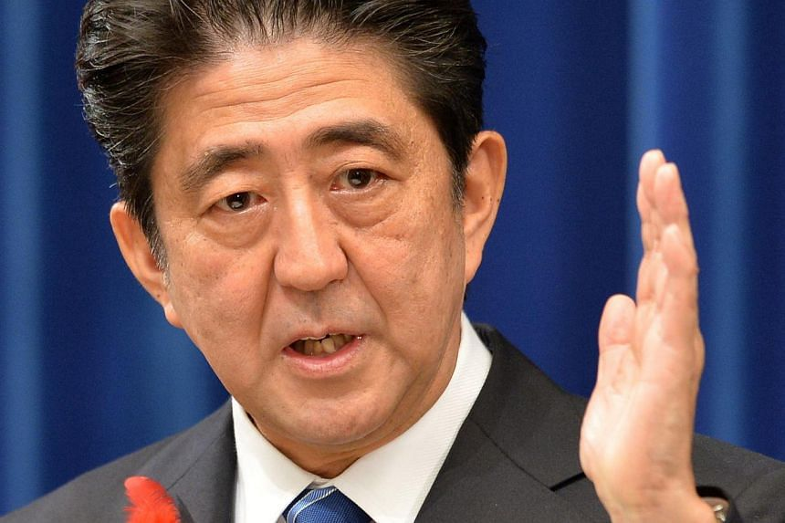 """Japanese Prime Minister Shinzo Abe announces the hike Japan's sales tax at a press conference at his office in Tokyo on Oct 1, 2013. Japan's economy is expanding and deflation is coming to an end due to Mr Abe's """"Abenomics"""" stimulus policies, the cou"""