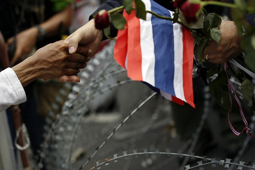 An anti-government protester shakes the hand of a police officer across barbed wire after giving him flowers at a barricade near a government building chosen as a protest site in Bangkok, Nov 25, 2013. Thousands of anti-government protesters ma