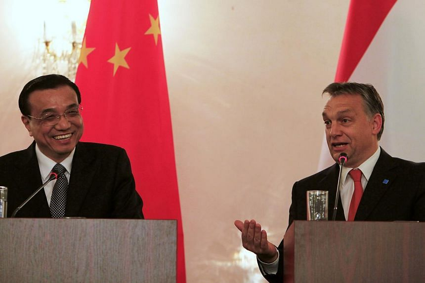 China's Premier Li Keqiang laughs as Hungary's Prime Minister Viktor Orban (right) speaks during a joint news conference with Serbian PM Ivica Dacic (unseen) in Bucharest on Nov 25, 2013. Mr Li on Monday said that China will work with Hungary and Ser